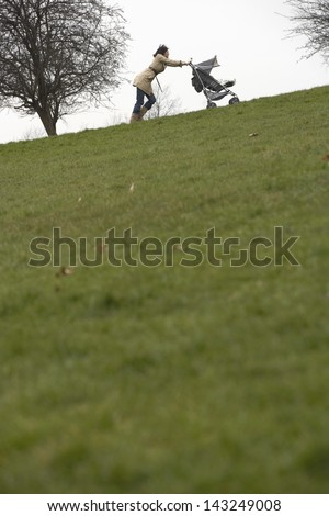 Young mother pushing stroller uphill in park - stock photo