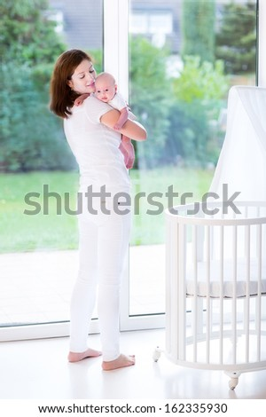 Young mother putting her newborn baby to sleep in a white bed with canopy next to a big window - stock photo