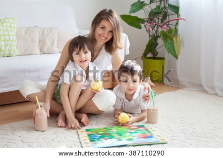 Young mother, read a book to her tho children, boys, in the living room, eating fruits and drinking smoothie, mother day concept - stock photo
