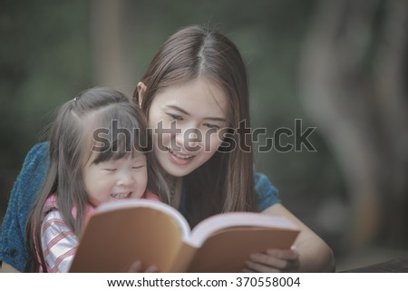 young mother reading a book to her cute daughter vintage style - stock photo