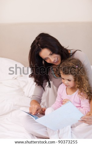 Young mother reading bedtime story for her daughter