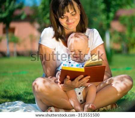 Young mother reading book to her little son at park