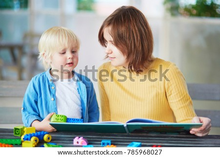 Young mother reading book to her son. Quality family time with kids