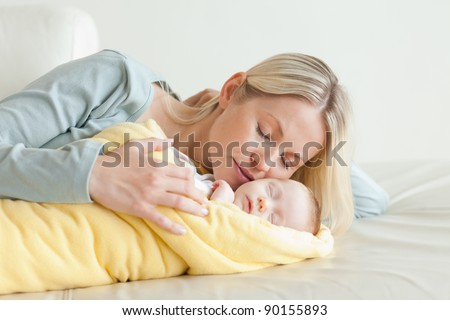Young mother relaxing next to her sleeping baby - stock photo