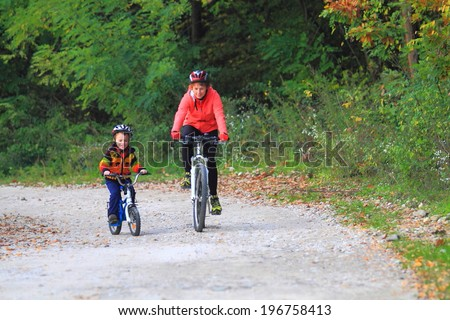 Young mother riding bike with small child on autumn road