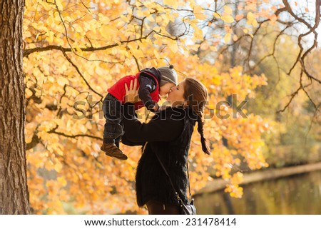 Young mother rising baby boy up - stock photo