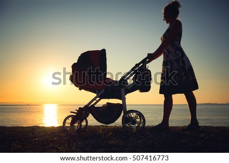 Young mother rolling baby stroller against beach sunset.