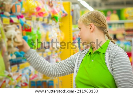 Young mother select kids toys in supermarket - stock photo