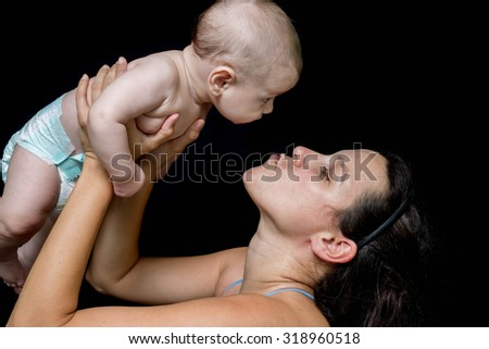 Young mother sending a kiss to  her little newborn baby on a black background - stock photo