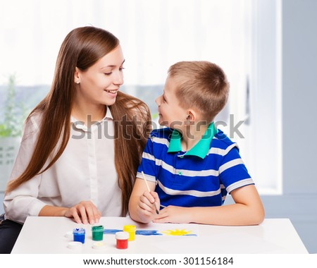 Young mother sitting at a table at home helping her small son with his homework from school as he writes notes in a notebook - stock photo