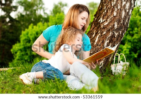 young mother sitting in grass under tree and reading book to her small daughter who is lying on knees of her mother and smiling