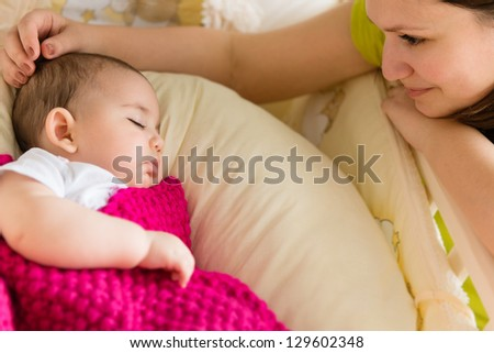 Young mother sitting near sleeping baby at home - stock photo