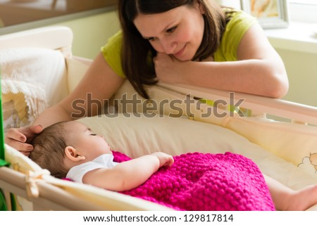 Young mother sitting near sleeping baby at home