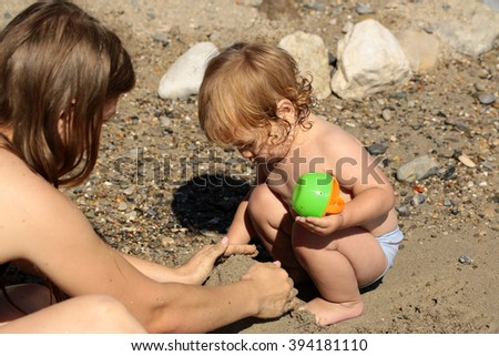Young mother sitting on sea beach sand near water playing with small cute child boy with plastic toys sunny day outdoor on natural background, horizontal picture - stock photo