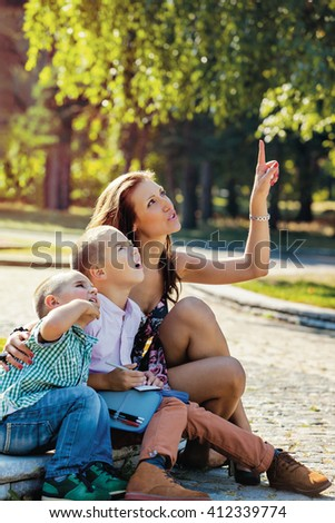 Young mother sitting with her children in the park, showing them something above with finger, they are looking with interest. - stock photo