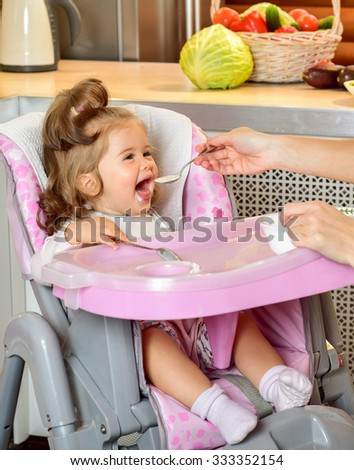 Young mother spoon-feeds the child. Feeding baby. Baby food. - stock photo