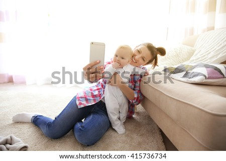 Young mother taking a selfie with her baby near the couch, close up - stock photo