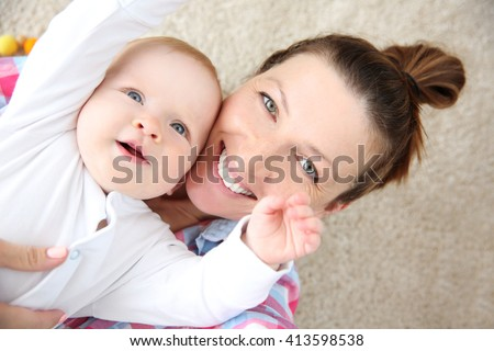 Young mother taking a selfie with her baby on the floor, close up - stock photo