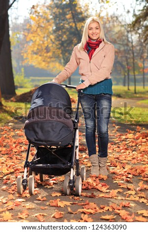 Young mother taking a walk in the park with her baby in a pushchair - stock photo