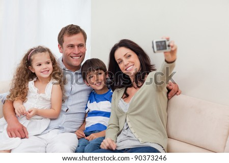 Young mother taking family photograph on the couch