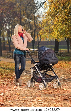 Young mother talking on a mobile phone during a walk in the park with her baby in a pushchair - stock photo