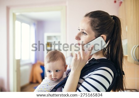 Young mother talking on a phone having her baby in a carrier