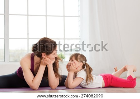 Young mother talking with daughter during yoga exercise in fitness studio with big windows on background - stock photo