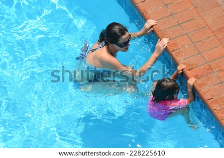Young mother teach her child (girl age 04) to swim  in a swimming pool. - stock photo