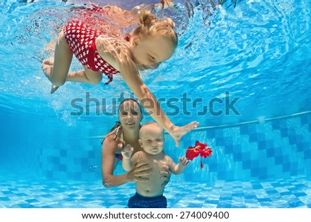 Young mother teaches to swim 10 month old baby - dive with cheerful child deep into the blue water, healthy lifestyle and children underwater swimming lessons with an instructor in the pool - stock photo