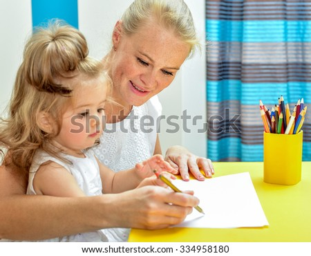 Young mother teaching little daughter draw pencils. Interior of the room.