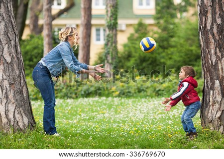 Young mother throwing a ball to her cute little son while playing in a park - stock photo