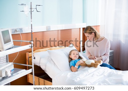 Young mother visiting her sick little daughter in hospital