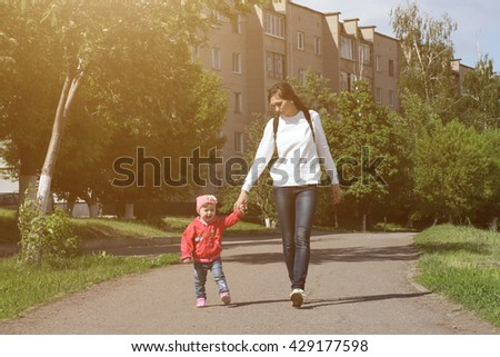 Young mother walking with a child on sidewalk