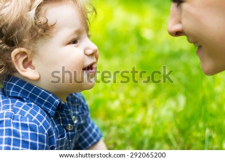 Young mother walking with a little boy. Child Outdoors.Mother and baby walk - stock photo