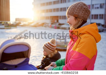 Young mother walking with baby child stroller in winter at sunset. - stock photo