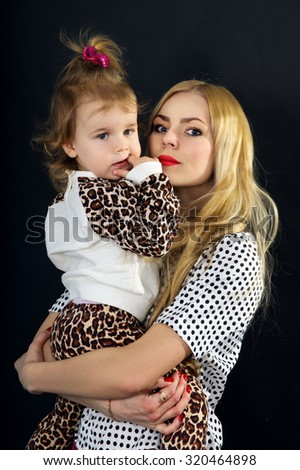 Young mother with a child on a black background in the studio - stock photo