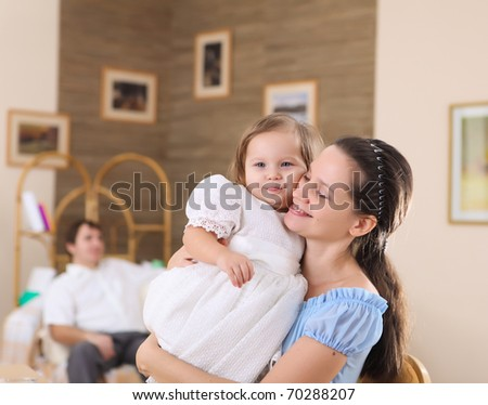 young mother with a daughter at home together playing and cuddling - stock photo