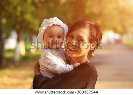 young mother with a small child in her arms in nature