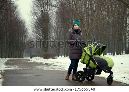 young mother with a stroller on a walk in winter park - stock photo