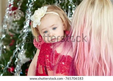Young mother with a tired baby girl in front of xmas tree. Christmas family portrait. Winter holiday Xmas and New Year concept