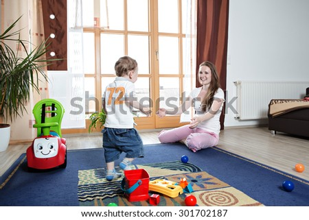 young mother with a toddler by playing at home