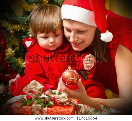 Young mother with  baby  at Christmas tree - stock photo