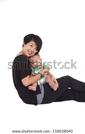 Young mother with baby boy. Sitting on white cloth and side view