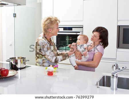 Young mother with baby girl and the grandmother in a modern kitchen setting. - stock photo