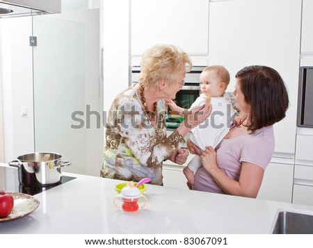 Young mother with baby girl and the grandmother in a modern kitchen setting.