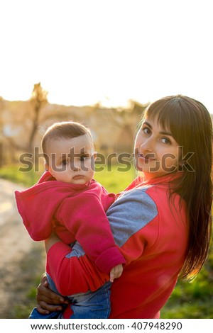 Young mother with baby on sunset - stock photo