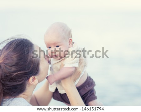 Young mother with baby on the beach - stock photo