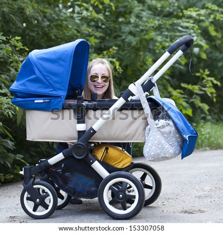 Young mother with baby stroller for a newborn