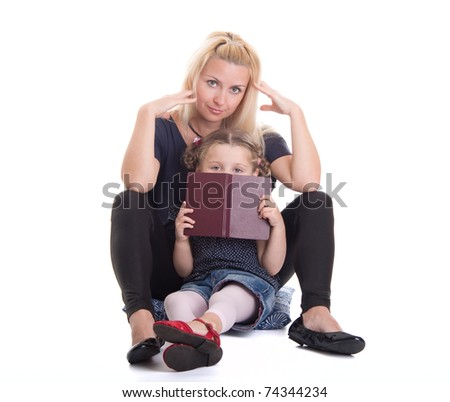 Young mother with beautiful daughter reading book on white background - stock photo