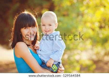 Young mother with child outside on a summer day